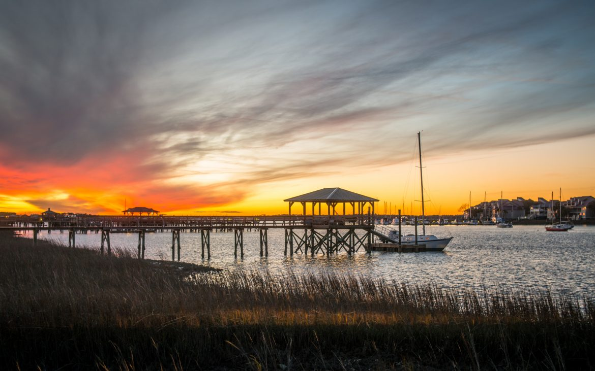 A dramatic sunset rises above residential boat docks at Folly Beach