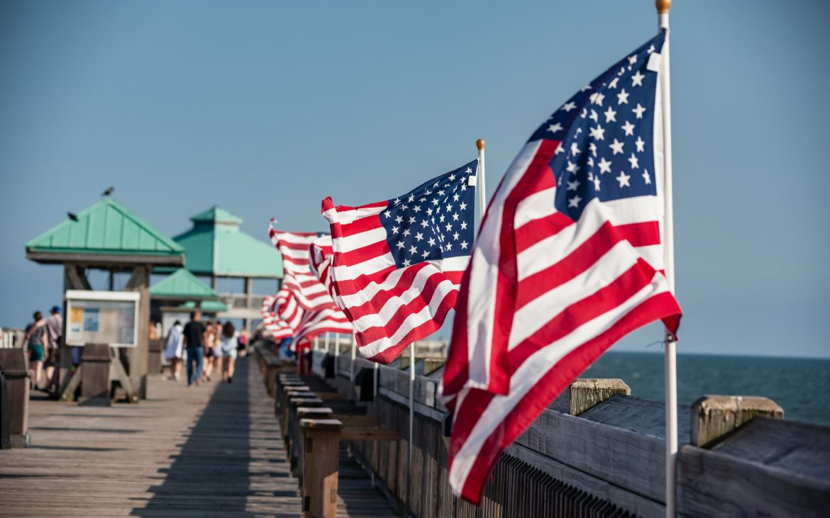 Small American flag on a flagpole blowing in the wind at the beach on a pier in Charleston, South Carolina