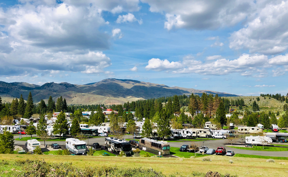 View of RV park amidst mountains and pine trees on beautiful day