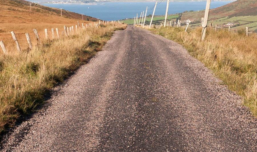 Rugged gravel road near a coastal area.