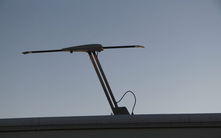An extended TV antenna on the roof of an RV.