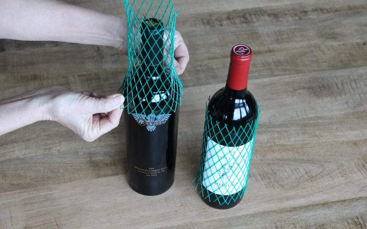 Fastening protective netting over bottles of red wine.