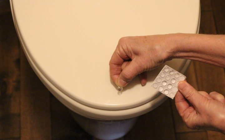Applying self-adhesive silicone dimples to a toilet lid.