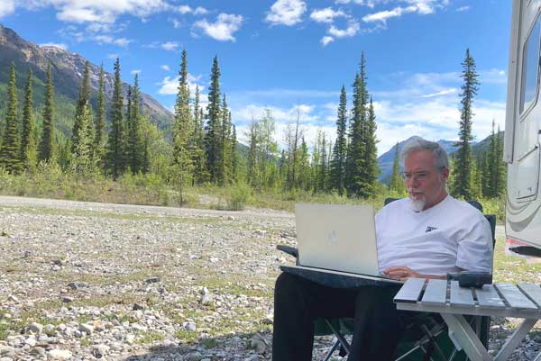Jim Nelson works on his laptop in British Columbia with rugged trees and mountains in the distance.