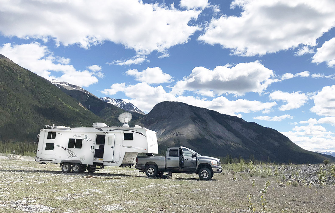 An RV parked amid Alaska Mountains with satellite dish deployed.