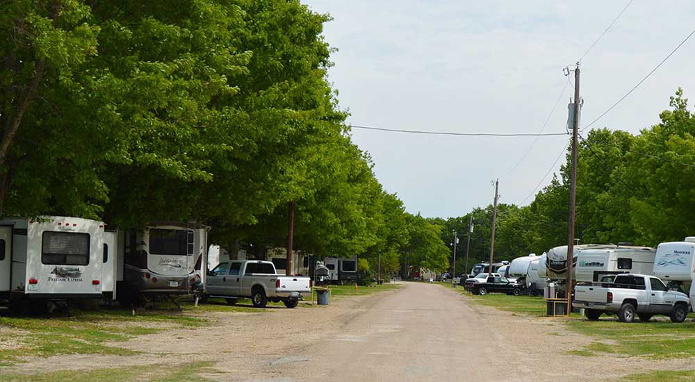 RVs parked under shade trees at Riverview Campground in Waco