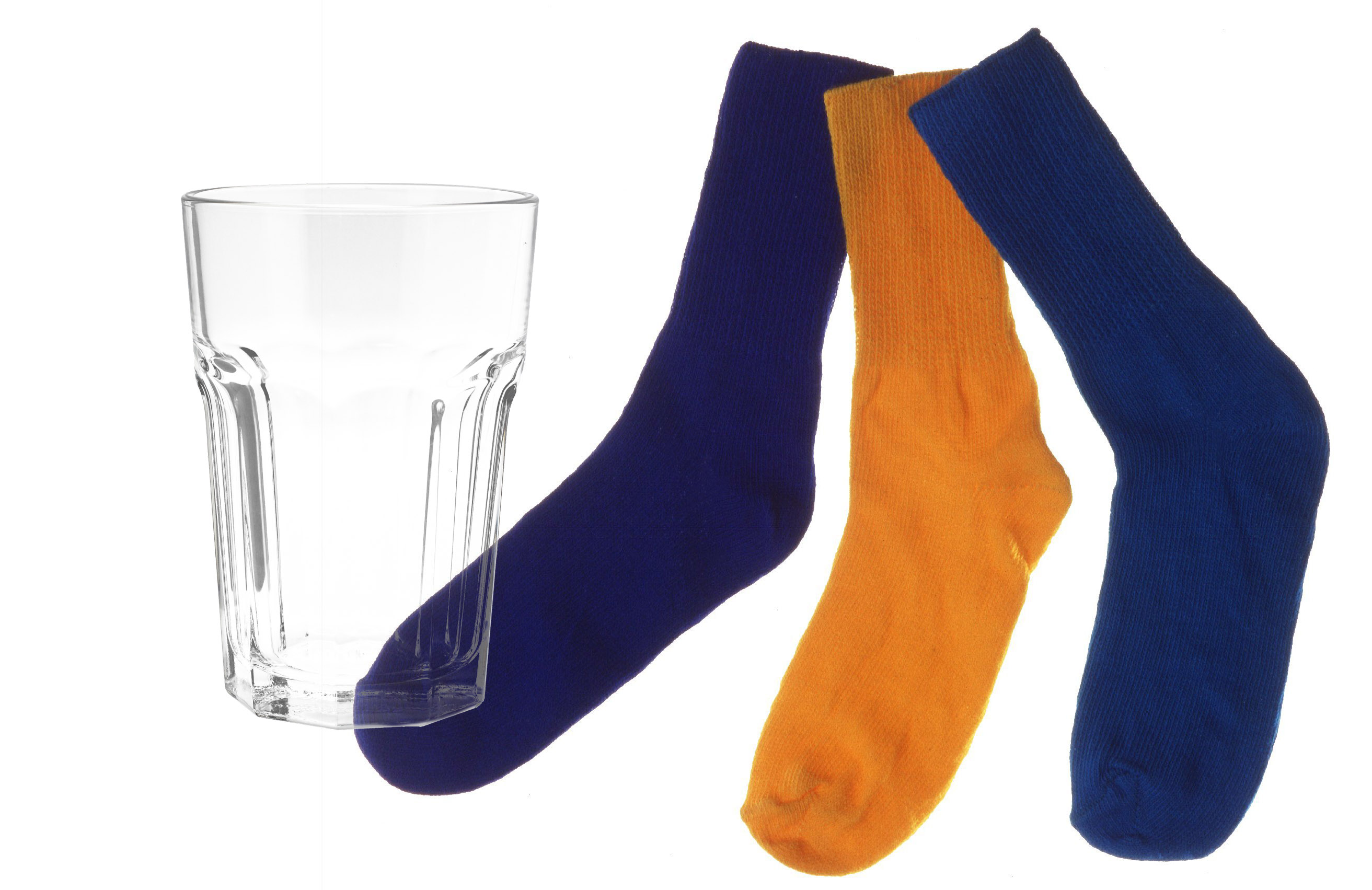 A clear water glass juxtaposed with some socks.