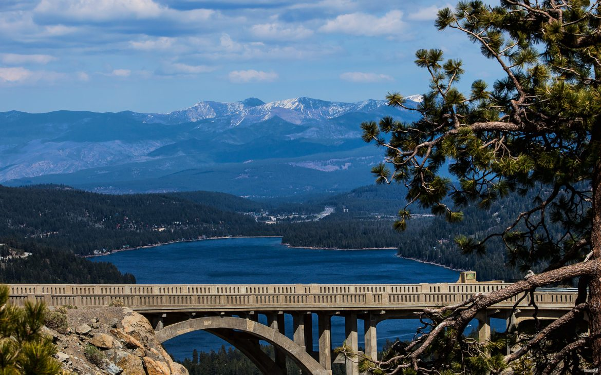 Scenic view of the Donner Memorial Bridge at Donner Pass at the Summit with gorgeous snow capped mountains in the distance and the blue waters of Donner Lake beneath the bridge