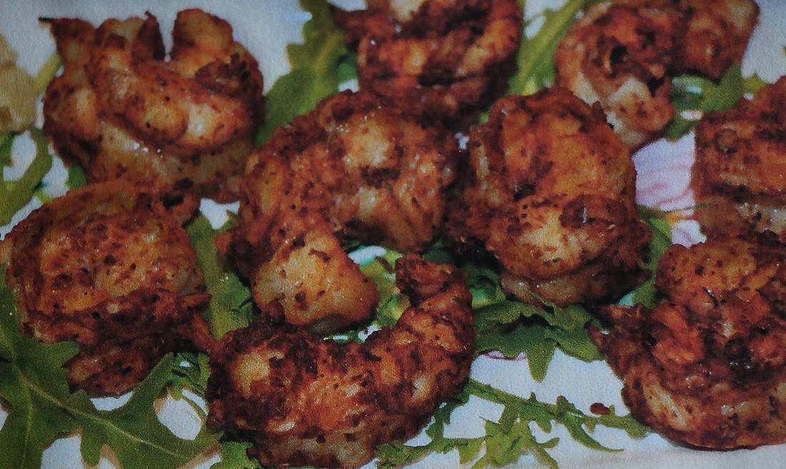 Spicy barbecued shrimp cool off on a bed of greens.