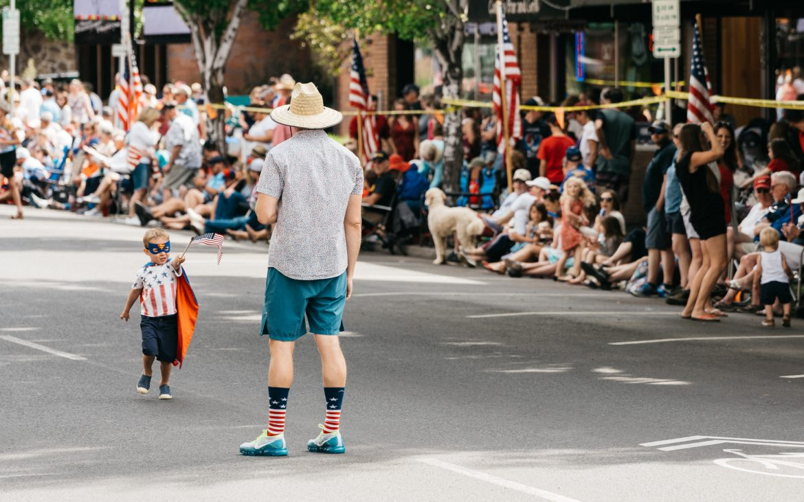 Little boy carrying small American flag with Dad at street parade