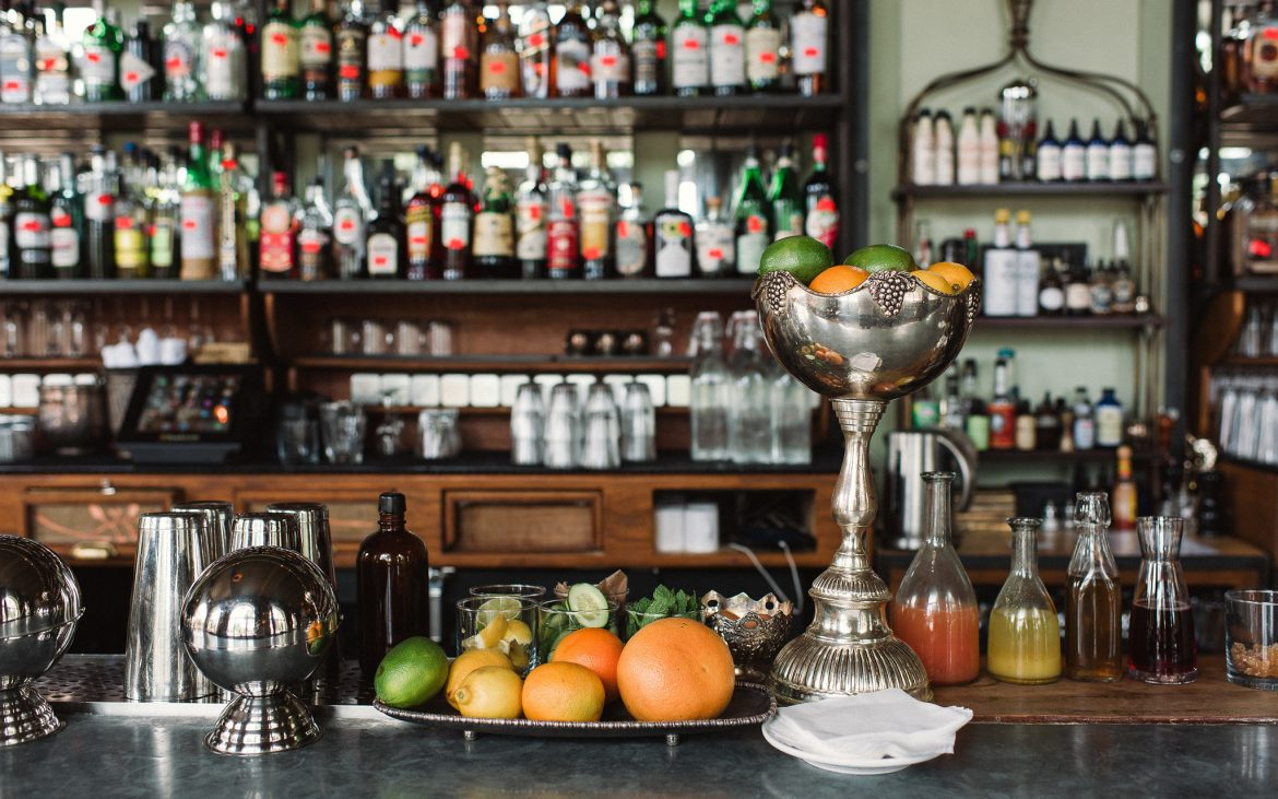 Beautiful bar with silver fixtures and botanical liquors in background and fruit