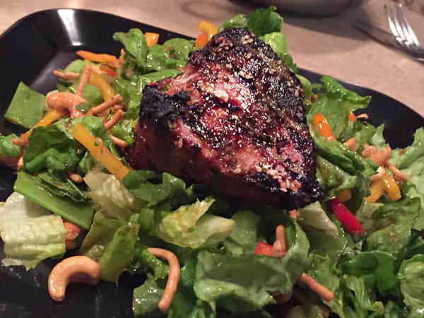 A grilled salmon steak sits atop a bed of greens, cashews and noodles