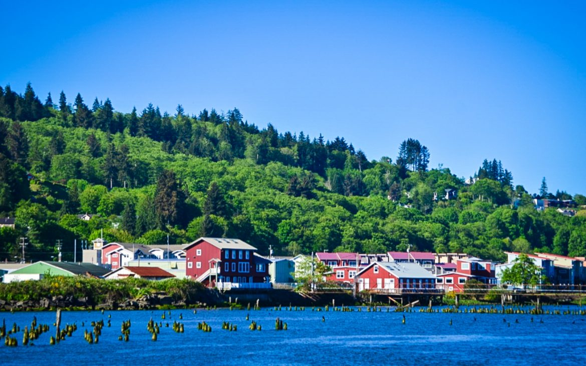 Beautiful colorful houses along blue river with pine trees on hillside