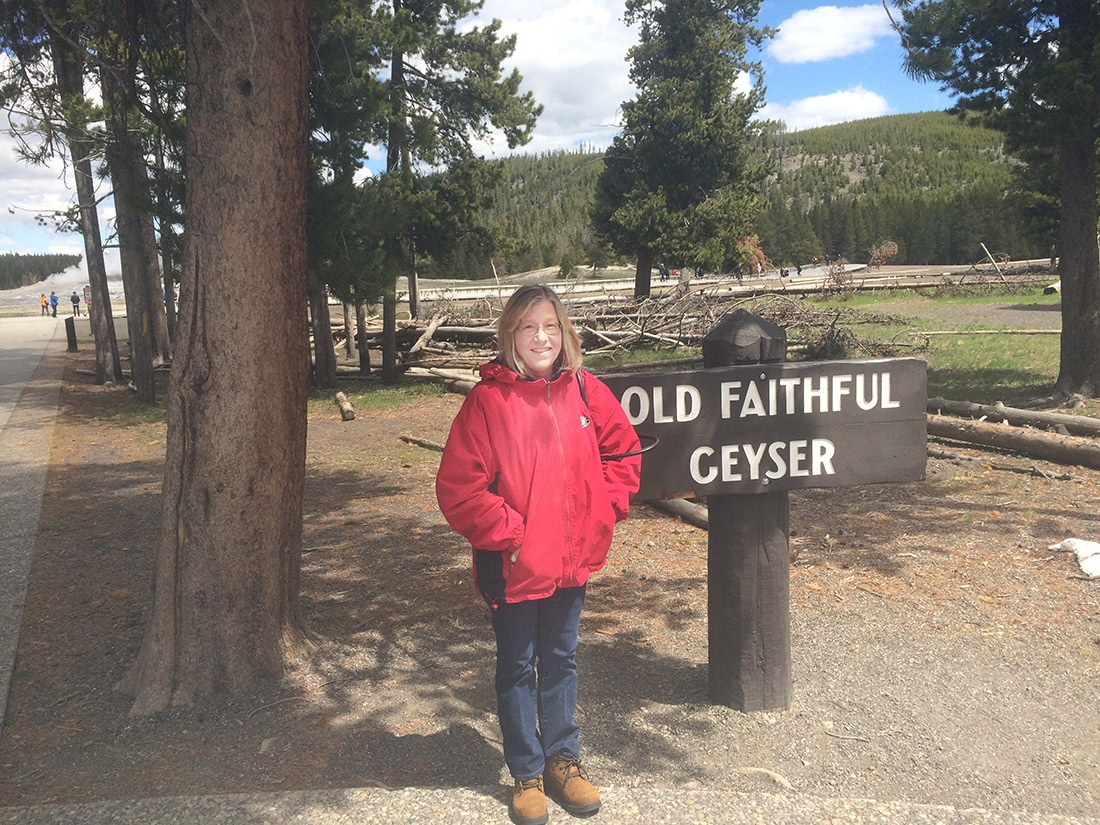 Standing in front of the Old Faithful Geyser sign.