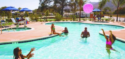 Men and women throwing an inflatable ball around in pool
