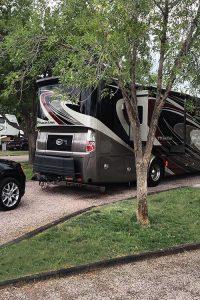 Black Jeep Grand Cherokee parked behind large RV