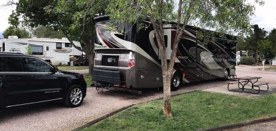 Black Jeep Grand Cherokee parked behind large RV
