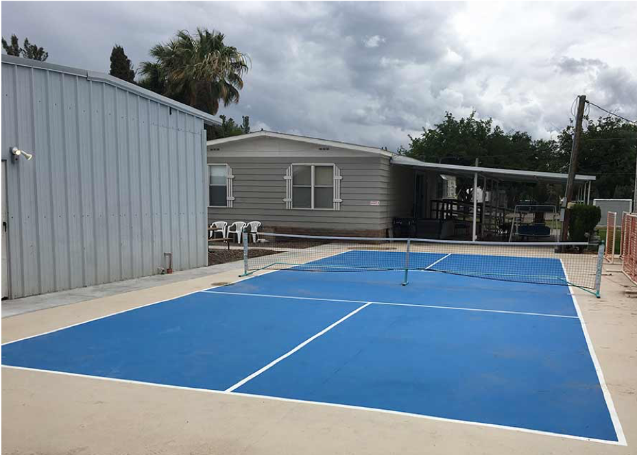 Blue tennis court with gray building in background