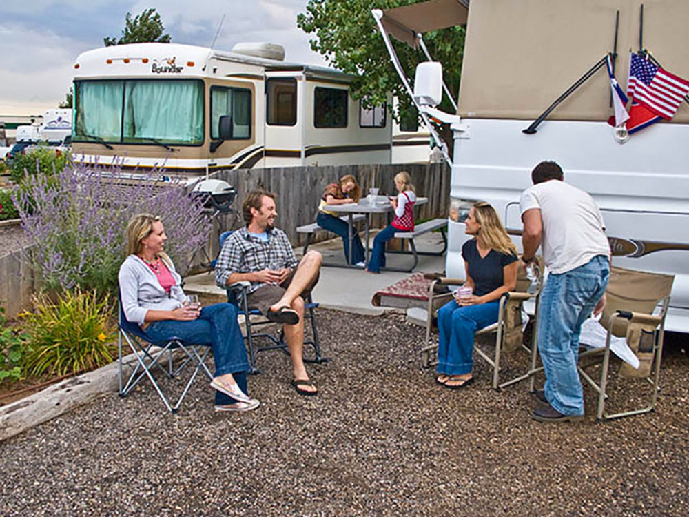 Campers relaxing in front of an RV