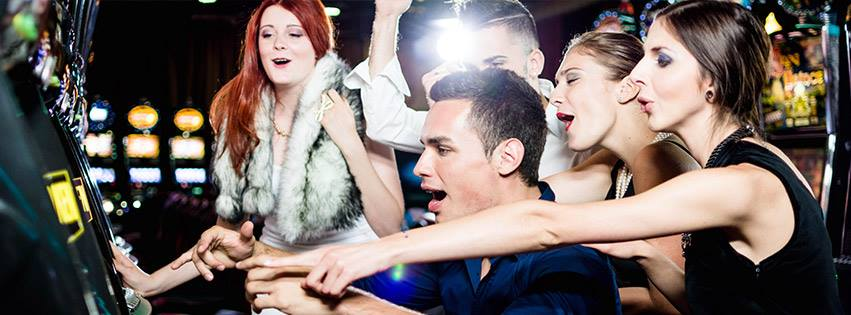 Men and women having fun, dressed in party clothes gambling at casino