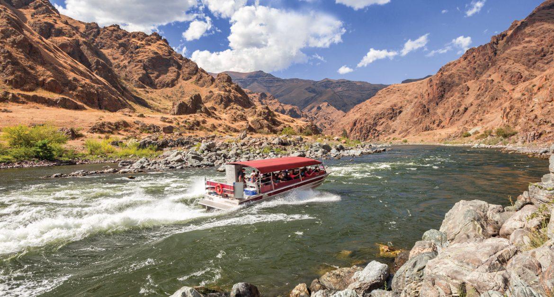 Red boat speeding down river in the desert