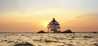 White and red screw-down lighthouse in the bay against a setting sun