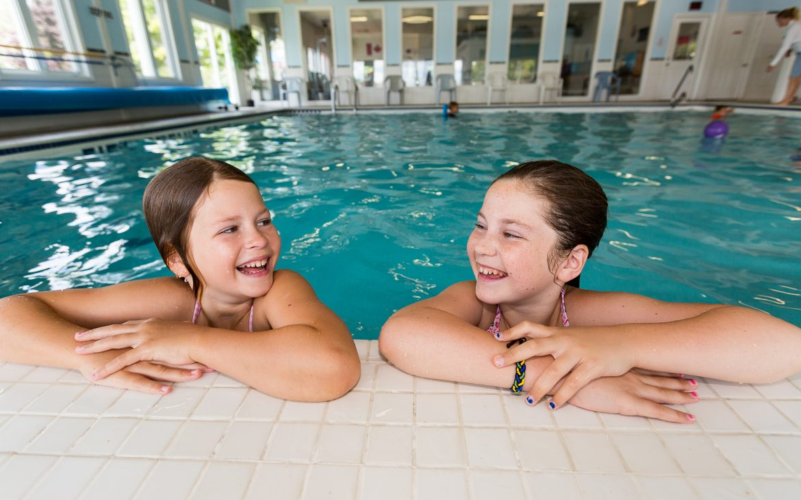 two young girls playing in indoor pool
