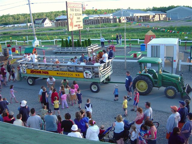 People watching green tractor pulling wagon