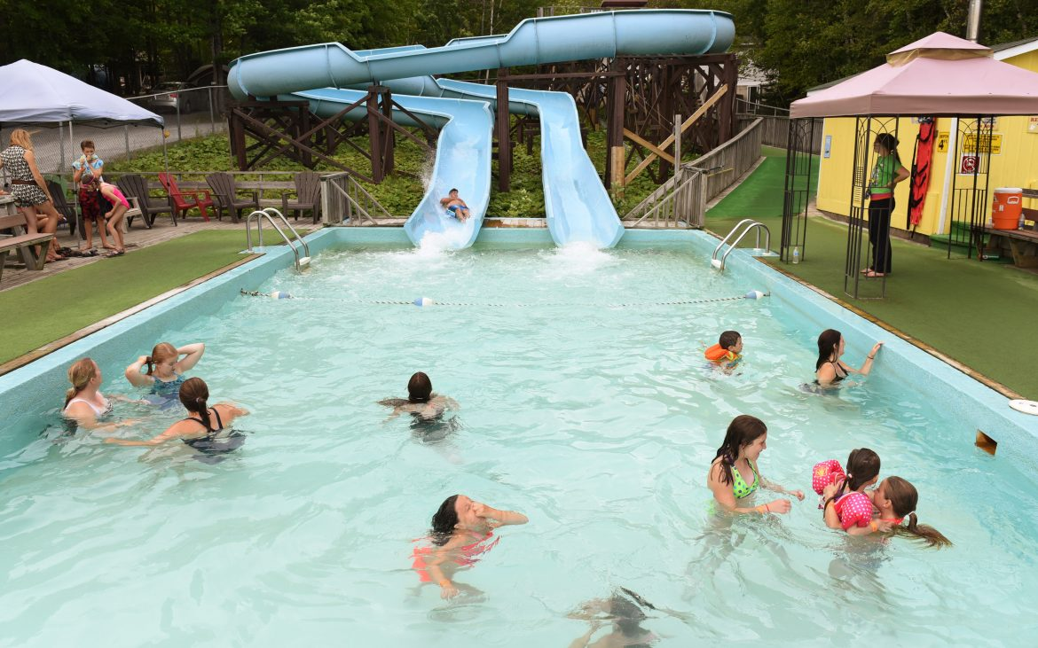 Mothers and children playing in pool at base of blue waterslide