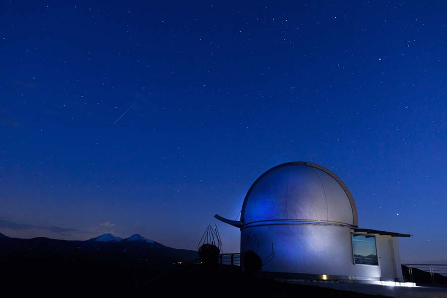 The Palomar Observatory sits under the stars of a night sky.