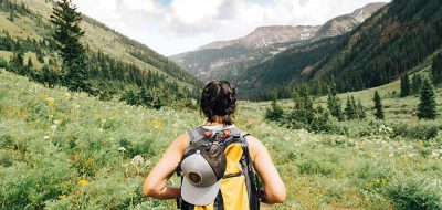 Woman hiking wearing yellow backpack in grassy area with mountains in foreground