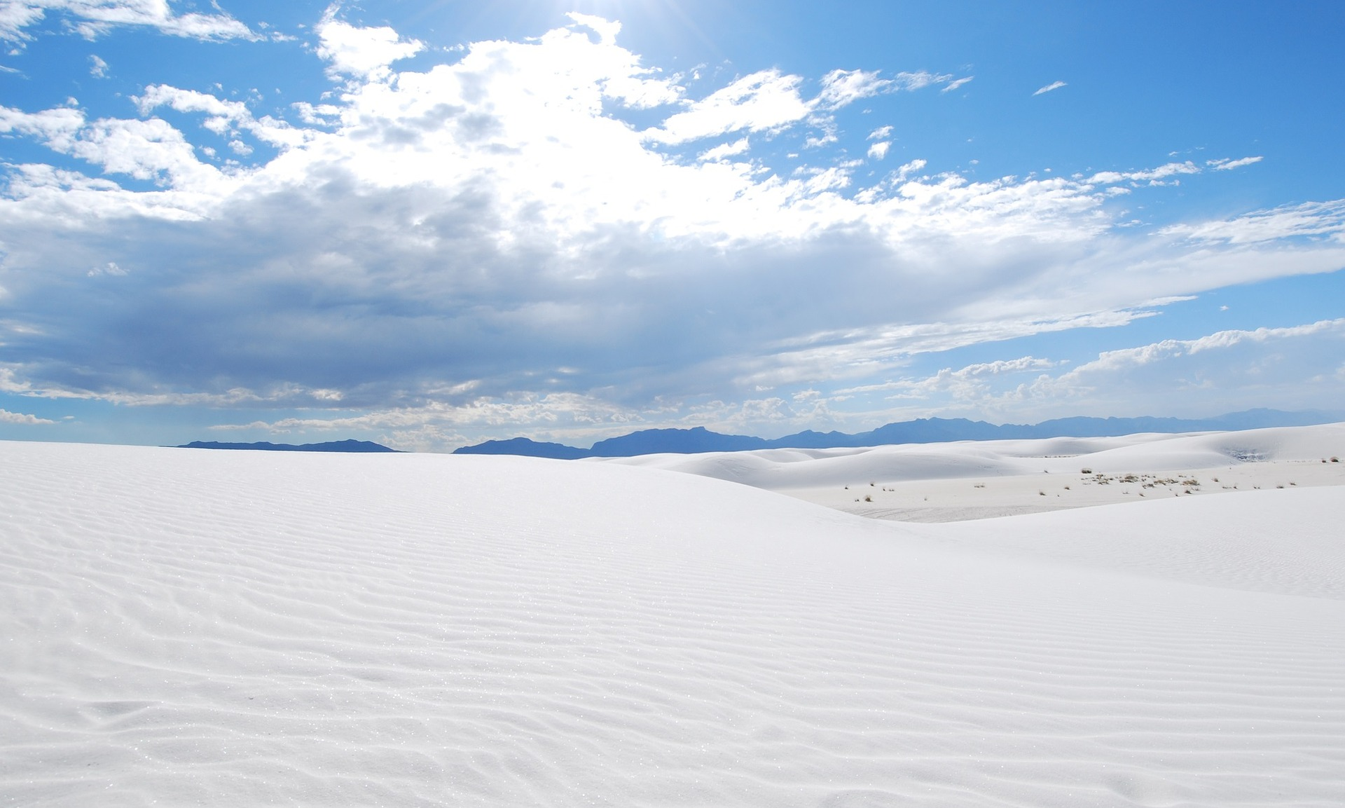 White, wind-blown desert sands with mountains on the horizon.
