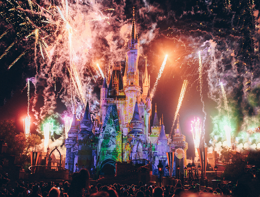 Colorful lit Disney castle at night with fireworks exploding