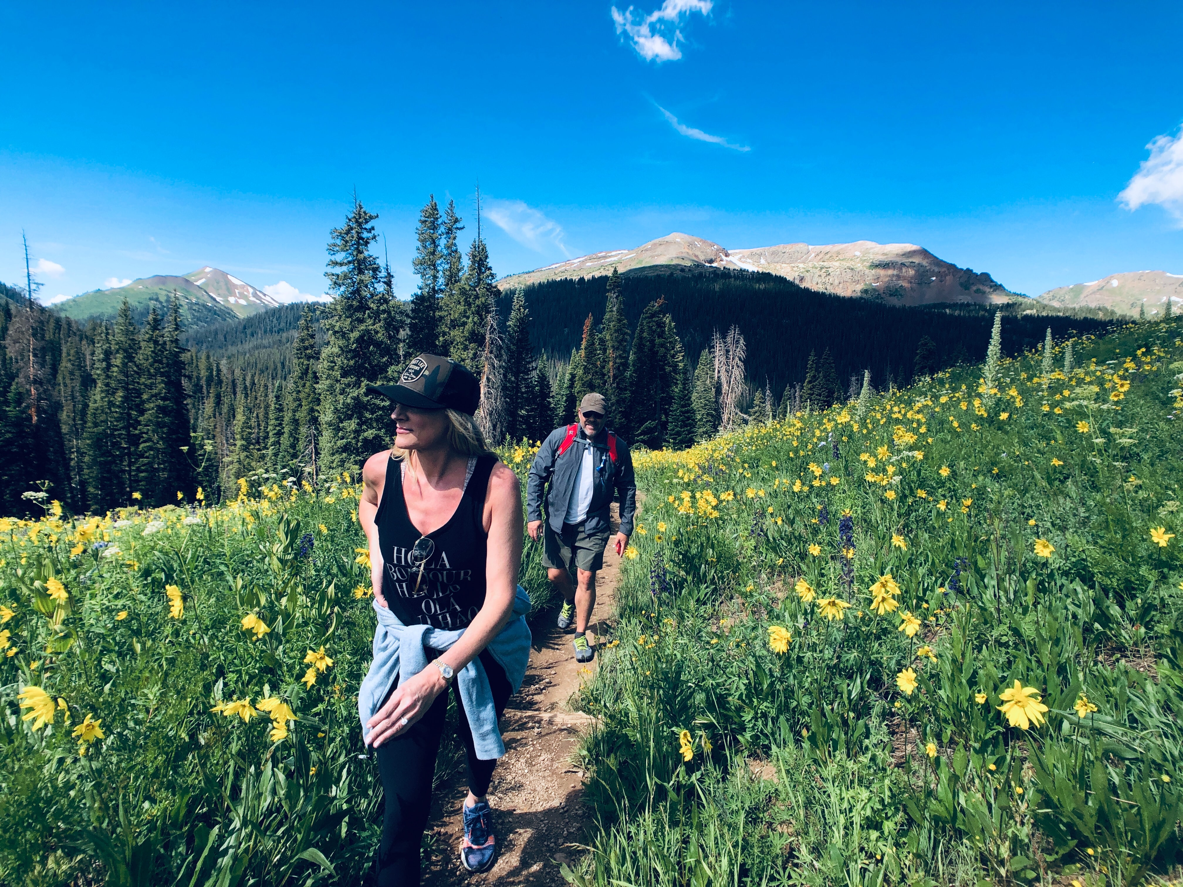A man and woman hike a mountain trail bordered on both sides by tall daisies.