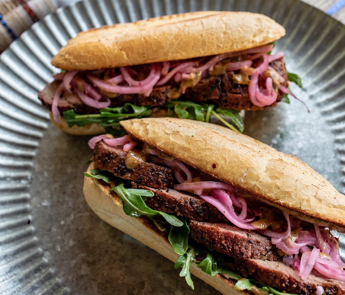 Tri-tip sandwiches with pickled onions, spinach and mustard sauce.