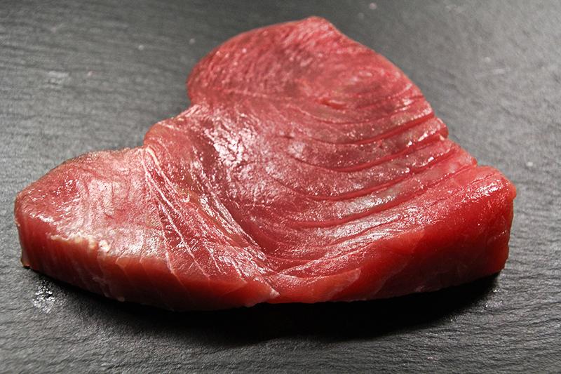 A cut of uncooked tuna steak