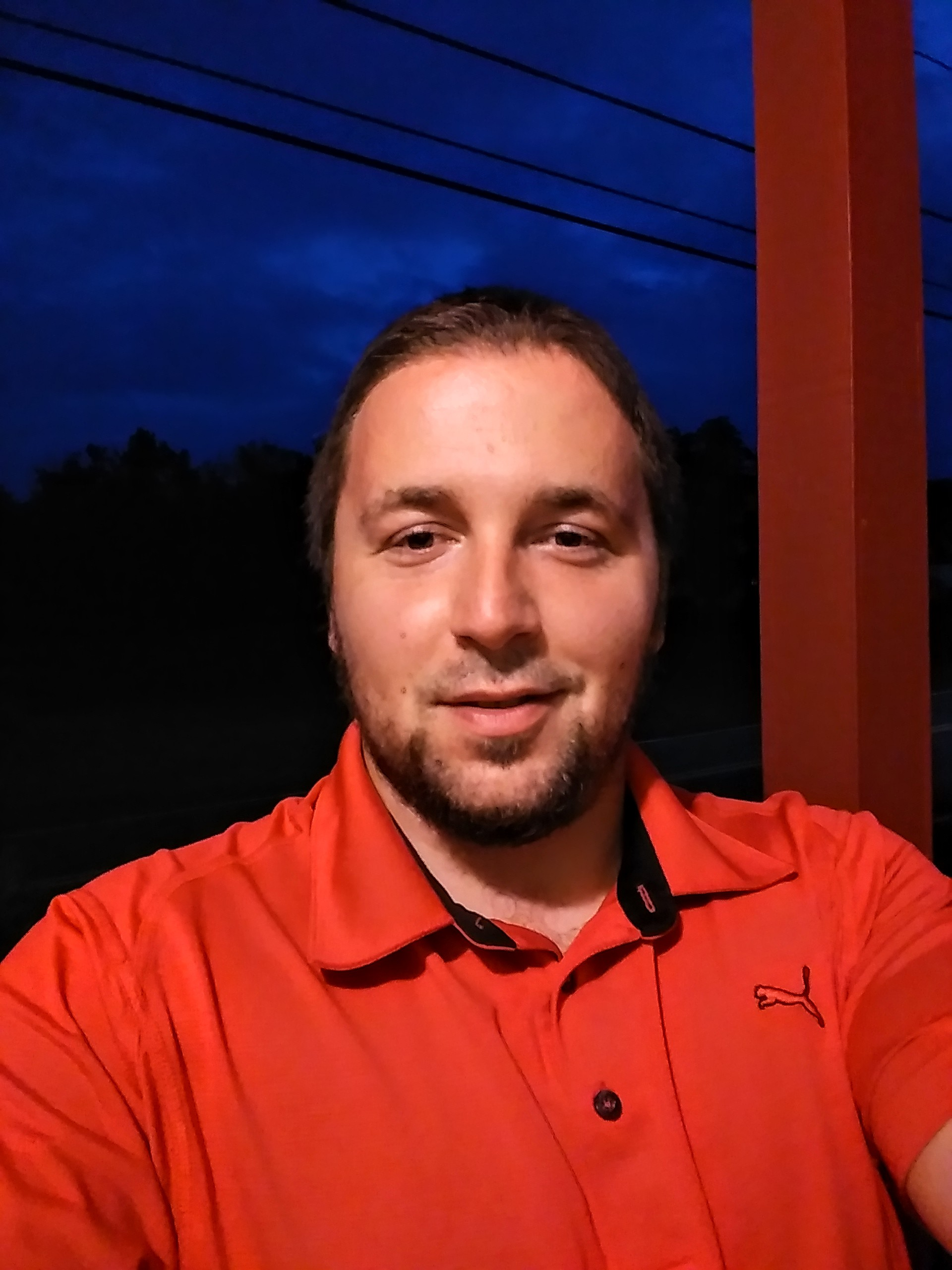 Man with beard and red shirt smiles at camera.