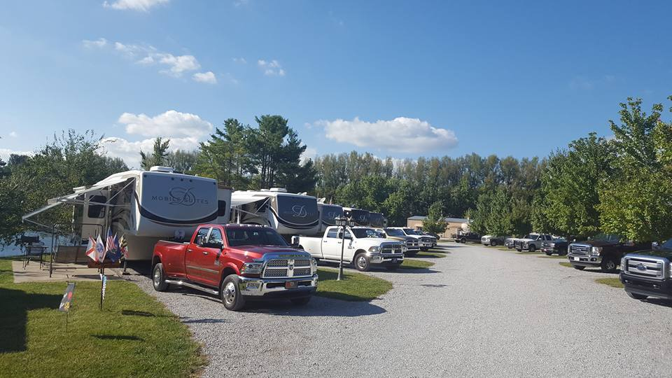 Pickup trucks parked in front of trailers along road