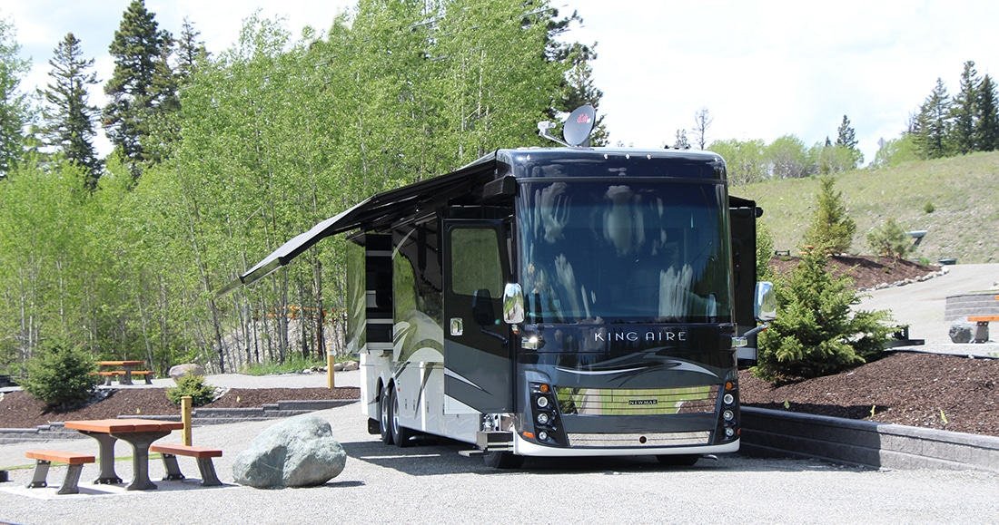 At an RV park, A motorhome camps with awnings deployed and shades and curtains drawn