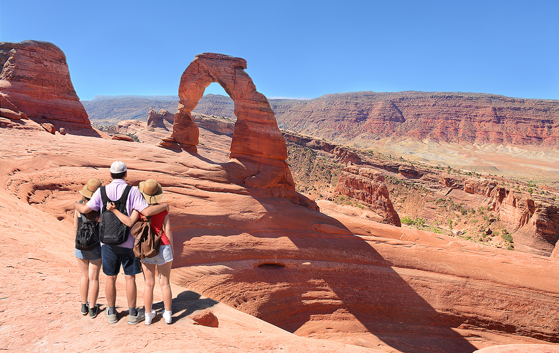 A family hiking on a clear day at Utah's Arches National Park.