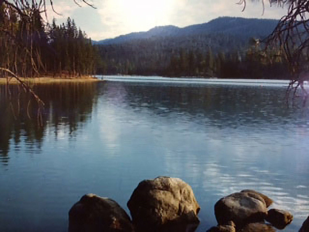 A lake reflects the sunny sky as forested mountains rise in the distance.