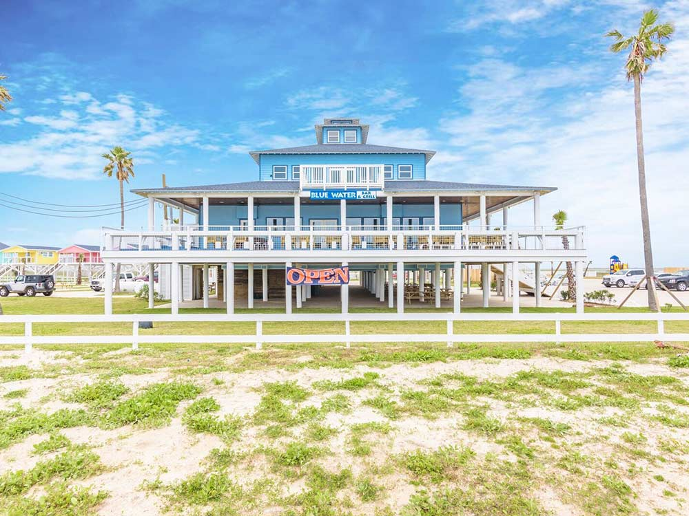 A two-story complex with sweeping balconies painted blue and sporting Victorian design faces the ocean at Blue Water RV Resort,