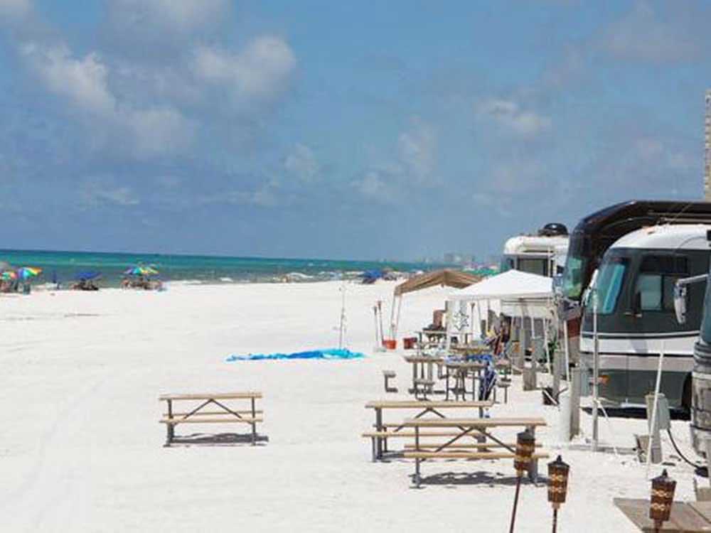 A row of RVs face the white-sand beach and turquoise waters of the Gulf of Mexico in Destin.
