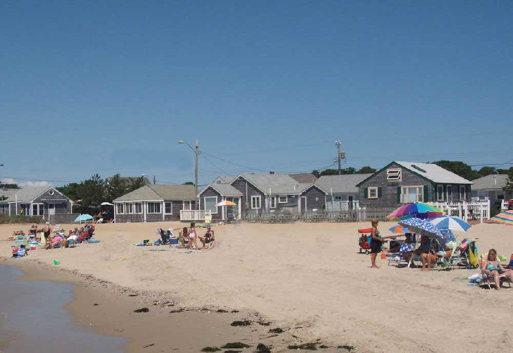 With umbrellas planted in the sand, sunbathers sit on folding chairs and towels on a Cape Cod beach.