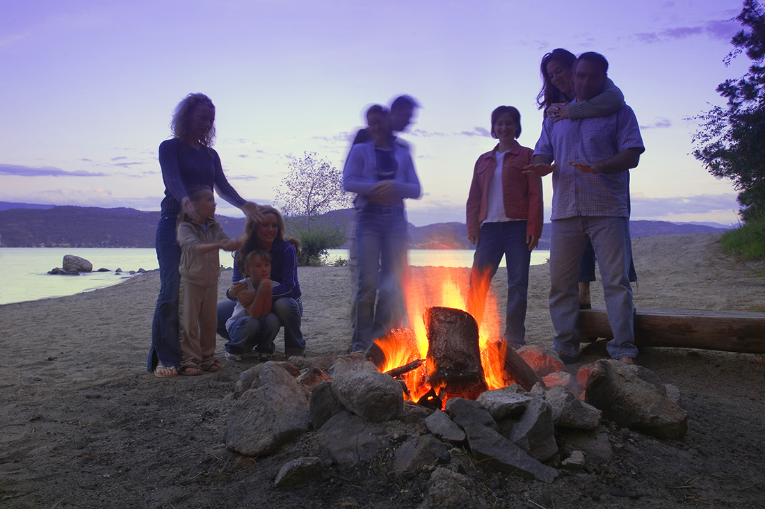 A family gathers around a campfire.