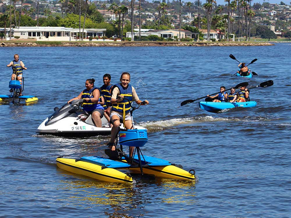 Smiling young people on sea cycles, kayaks and jet skis ply the waters of Mission Bay in San Diego.