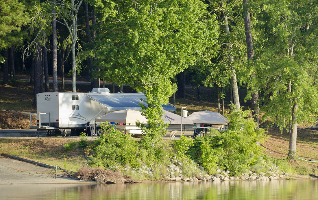 A travel trailer stays cool by camping on the water.