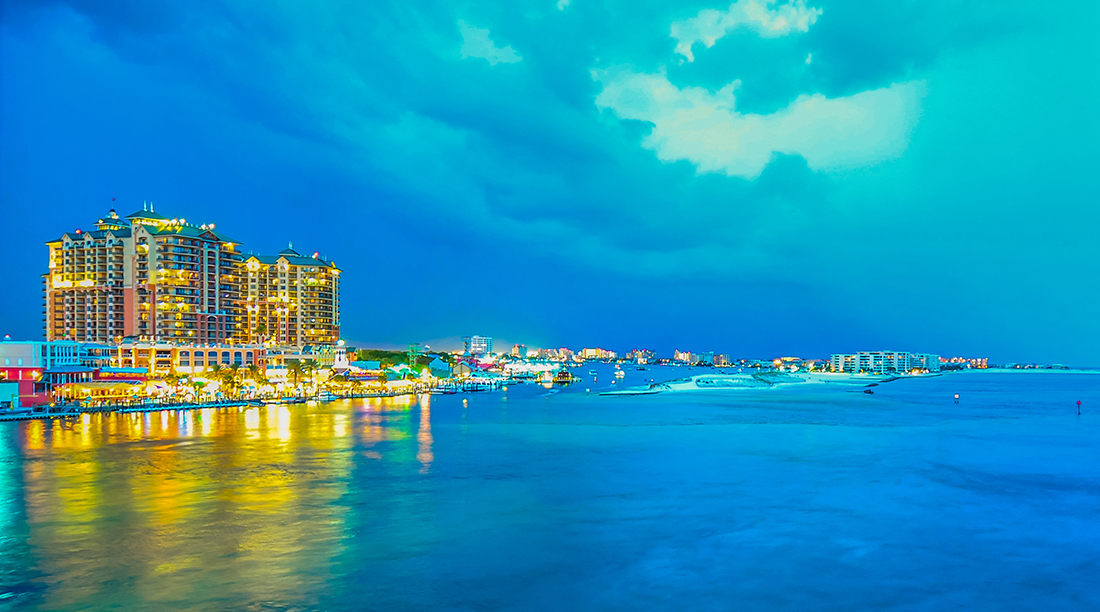 Luxury hotels cast yellow light on the ocean that borders Destin, Florida.