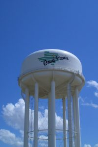 Large white water tower against blue sky