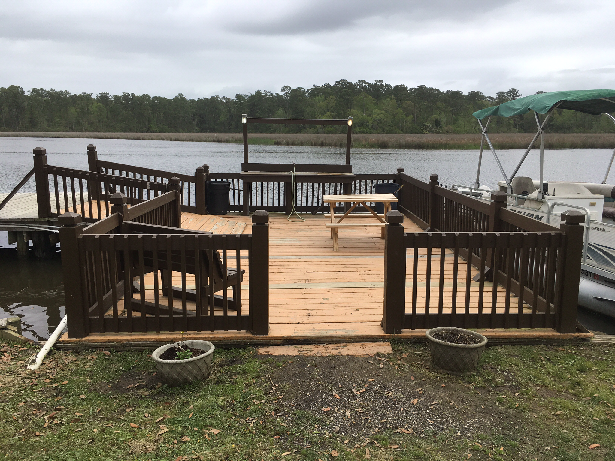 Wooden deck on river with boat alongside